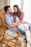 Young couple hugging in rocking chair and looking at each other Stock Images