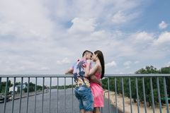 Young couple hugging and smiling each other walking on a bridge.  Stock Photo