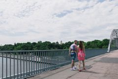 Young couple hugging and smiling each other walking on a bridge.  Stock Photography