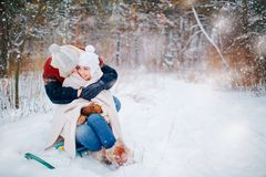 Young couple hugging on snow in winter park Stock Photo