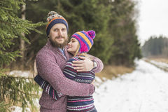 Young couple hugging in winter forest Stock Photo