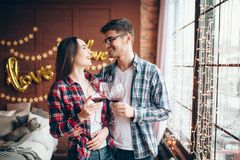 Young couple hugs against large window from floor Stock Image