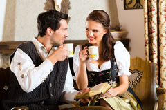 Young couple in a hunter's cabin drinking tea Royalty Free Stock Photo