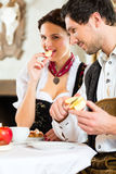 Young couple in a hunter's cabin eating Stock Image
