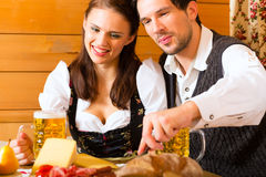 Young couple in a hunters cabin eating Stock Photo