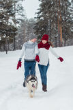 Young couple with a Husky dog walking in winter park, man and woman playing and having fun with dog. Stock Photos