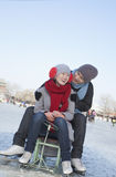 Young Couple Ice Skating, Sitting on Ice Sled Stock Photos