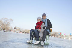 Young Couple Ice Skating, Sitting on Ice Sled Royalty Free Stock Image