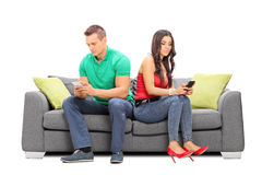 Young couple ignoring each other seated on a sofa Royalty Free Stock Photography