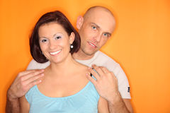 Young couple indoors. Young couple standing on the orange background Royalty Free Stock Image