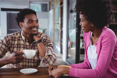 Young couple interacting with each other in cafeteria Stock Image