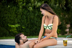 Young couple interacting with each other at poolside Royalty Free Stock Photography
