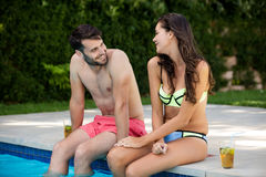 Young couple interacting with each other at poolside Royalty Free Stock Photo