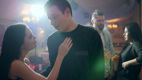 Young couple in intimate atmosphere on background of bright lights in club stock video
