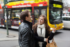 Young Couple In Jackets Communicating Street. Young women pointing while communicating with men on road side stock image