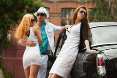 Young couple in love and jealous girl next to vintage car  Stock Image