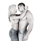 Young couple in jeans hug. Black and white shot of Young couple in jeans hug , studio shot royalty free stock images