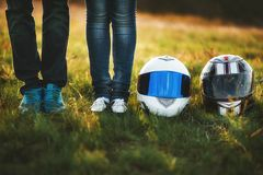 A young couple in jeans is standing next to two motorcycle helmets stock images