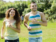 Young couple of joggers doing running at park Stock Photo