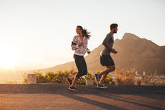 Young couple jogging on country road. Young couple jogging early in morning, with women looking back over her shoulder. Young men and women running outdoors on a Stock Photos