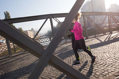 Young  couple jogging. Healthy young  couple jogging in the city  at early morning with sunrise in background Stock Image