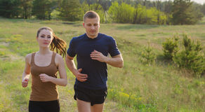 Young couple jogging outdoors. Young men and women jogging outdoors. Hands in motion blur Stock Photo