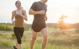 Young couple jogging outdoors. Young couple running at sunset outdoors. Solar flare illuminates a couple back Stock Photo