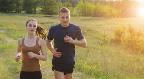 Young couple jogging outdoors. Young couple running at sunset outdoors. Solar flare illuminates a couple back.Hands in motion blur Stock Images