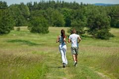 Young couple jogging outdoors in summer. Young couple jogging together outdoors in summer, shallow DOF Stock Photos
