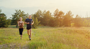 Young couple jogging outdoors. Sunset, glare from the sun illuminates a couple Stock Images