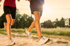 Young Couple Jogging in Park. Legs View Of A Couple Jogging Outdoor in the Park Royalty Free Stock Image