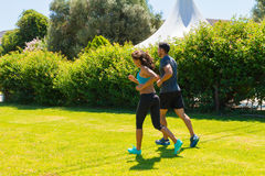 Young couple jogging at the park in a summer morning Stock Photos