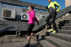 Young  couple jogging on steps Royalty Free Stock Photo