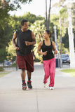 Young Couple Jogging On Street Stock Image