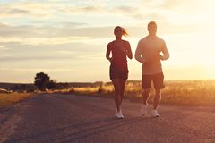 Young couple jogging in the suberbs after sunset royalty free stock photos