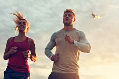 Young couple jogging in the suberbs after sunset royalty free stock photography