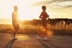 Young couple jogging in the suberbs after sunset stock image