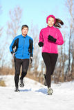 Young couple jogging in winter snow. Young couple running dressed warmly in fleeces and gloves jogging in sunshine across winter snow in the countryside royalty free stock photography