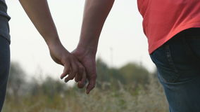 Young couple joining hands outdoor. Man and woman taking arms on nature background. Male and female hands comforting and Royalty Free Stock Photo