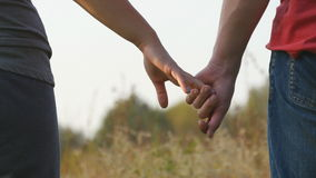 Young couple joining hands outdoor. Man and woman taking arms on nature background. Male and female hands comforting and. Stroking each other. Symbol of love stock video