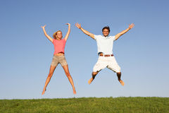 Young couple jumping in air Royalty Free Stock Image