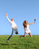 Young couple jumping on field Stock Image