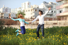 Young Couple Jumping In Meadow Stock Photos