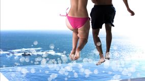 Young couple jumping into a swimming pool surrounded by white bubbles