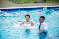 Young couple jumping in the swimming pool in a wedding suit and wedding dress. Sunny day. stock images
