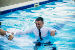Young couple jumping in the swimming pool in a wedding suit and wedding dress. Sunny day. Royalty Free Stock Photos