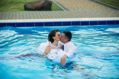 Young couple jumping in the swimming pool in a wedding suit and wedding dress. Sunny day.  Stock Image