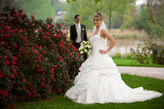 Young couple just married. He is looking to his bride while she is flirty with him after her wedding ceremony. outdoor in a park with a lot of greenery and Royalty Free Stock Photos