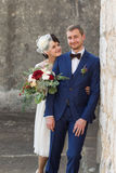 Young couple just married people. Standing near a wall and smiling Stock Images