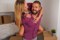 Young couple just move to their new apartment. Boy carrying girl Royalty Free Stock Photography